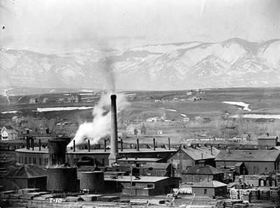 View of Burlington railyard in Sheridan, showing plume of steam from roundhouse and stacks of raw and treated railroad ties adjacent to the tie-treatment plant.  Courtesy of Wyoming Room, Sheridan County Fulmer Public Library.