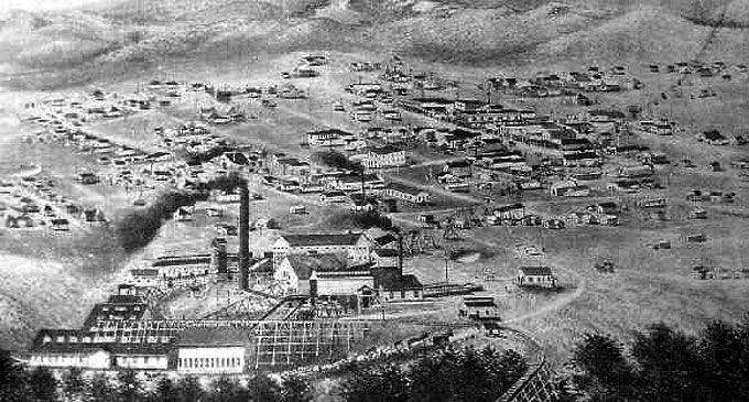 Encampment, Wyo., about 1903, with the copper smelter in the foreground and the ore-bearing aerial tramway rising to the right. Courtesy Wyoming Tales and Trails.
