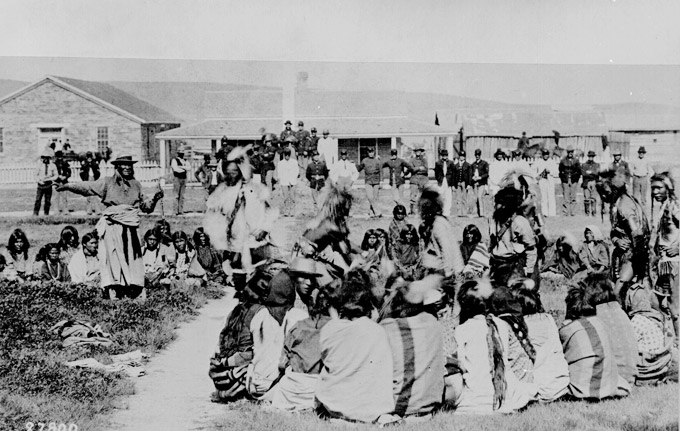 Chief Washakie, arm outstretched on left, with Shoshone dancers, U.S. troops and civilians at Fort Washakie, 1892. National Archives.