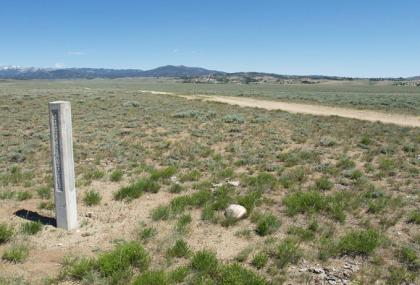 A nearly indistinct segment of Lander Trail next to the concrete marker near a county road west of South Pass, Wind River Mountains on the horizon. Will Bagley photo.