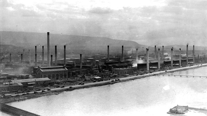 The Midwest Oil Company Refinery in Casper, shown here around 1920 with the North Platte River in the foreground, was later bought by Standard Oil. Blackmore Collection, Casper College Western History Center.