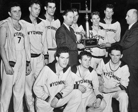 The 1943 UW men's basketball team, shortly after its 46-34 victory over Georgetown for the NCAA championship. Kenny Sailors is just to the right of the trophy.