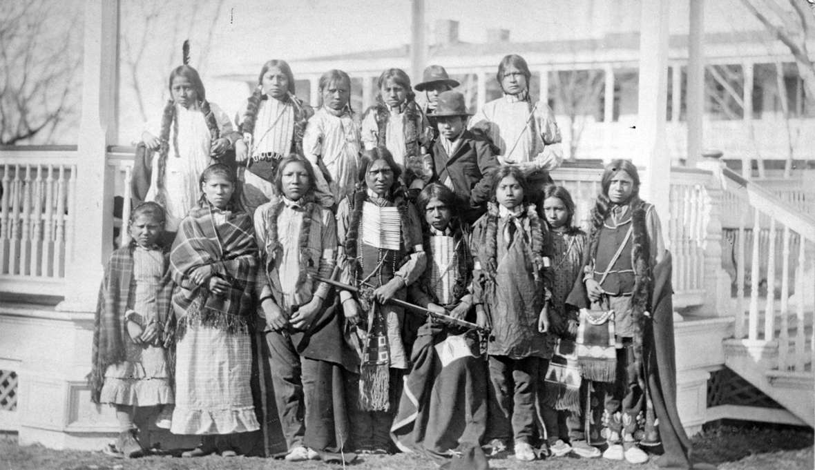 Northern Arapaho and Eastern Shoshone students at the Carlisle Indian School, 1881, shortly after their arrival from Wyoming Territory. Soon, the boys' braids would have been cut and they would no longer have been allowed to wear traditional dress. The two boys in hats are reportedly Shoshone. John Choate photograph. Click to enlarge
