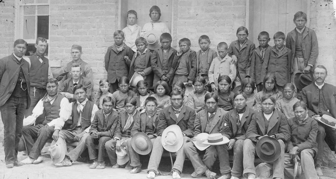 In 1883, the Episcopal priest Dr. John Roberts, seated at right with hat on his knee, founded the first mission school on the reservation. Later he was joined by the Rev. Sherman Coolidge, standing at far left, an Arpaho who had been raised in the family of a white Army officer and educated in the East. This photo of boys in the school may date from around 1890. Note that the boys are all wearing moccasins. American Heritage Center