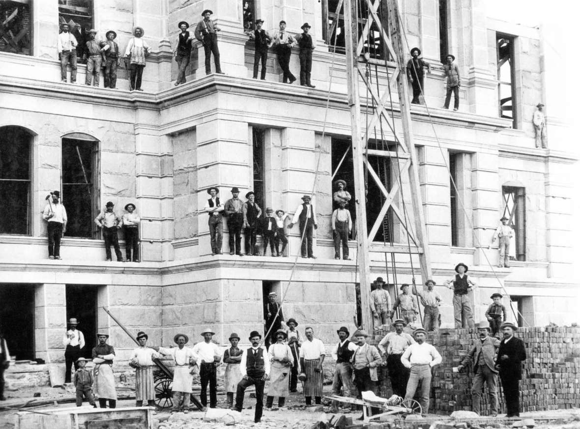 Workers on the walls and roof during construction of the Capitol's first addition, ca. 1889, which added wings to the east and west sides of the building. Wyoming State Archives.