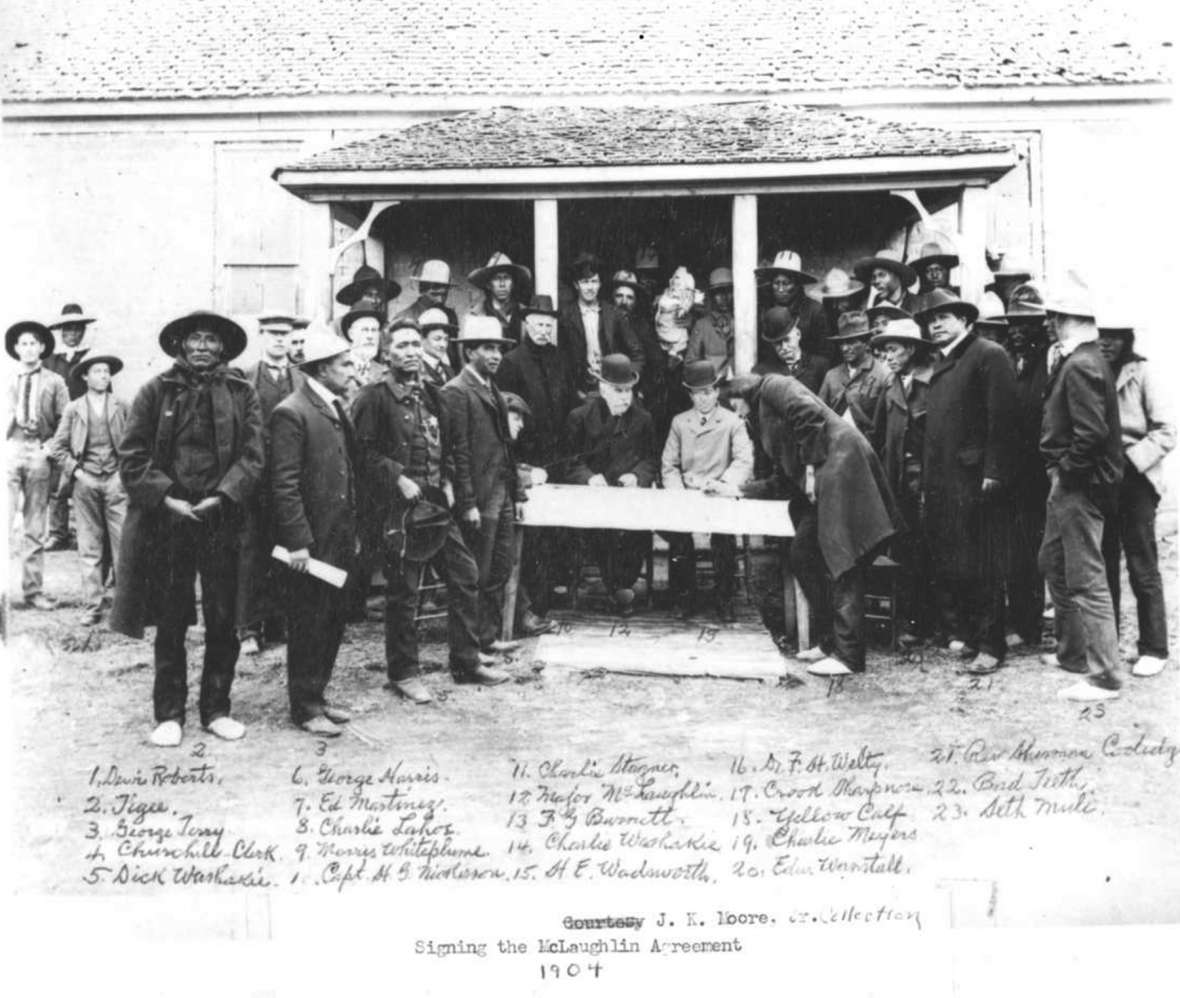 Shoshone and Arapaho men voted in 1904 to cede still more tribal land to the U.S. government. Here, the Arapaho leader Yellow Calf signs the agreement. Sherman Coolidge, at right in long black coat, was a prime proponent of the cession. American Heritage Center.