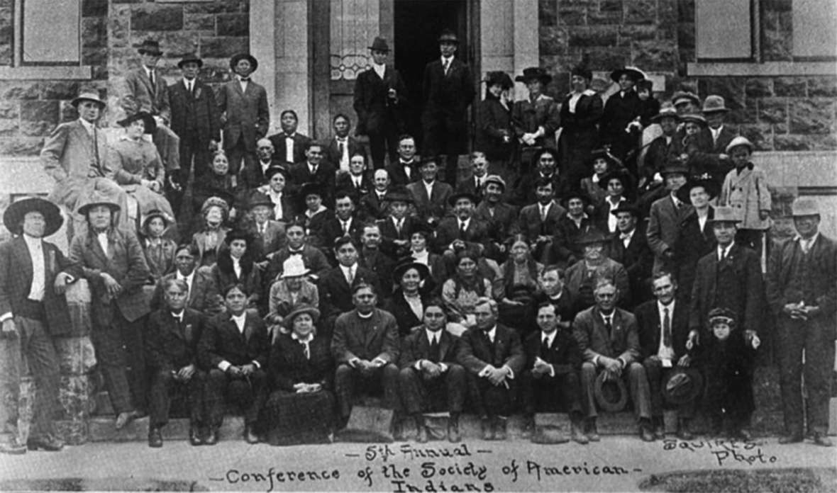 Attendees at the fifth annual conference of the Society of American Indians, 1915. Sherman Coolidge, in clerical collar, is near the center of the front row. His time in the Society softened his views on assimilation considerably, and he began to view Indian cultures as valuable. Wikipedia.