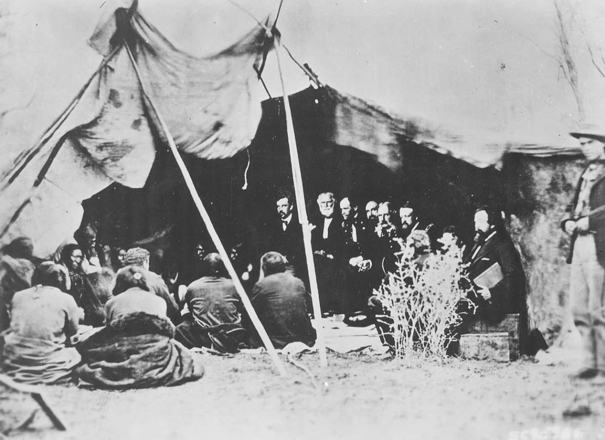 Government commissioners and tribal representatives during treaty negotiations at Fort Laramie, 1868. Alexander Gardner photo, Wikipedia.