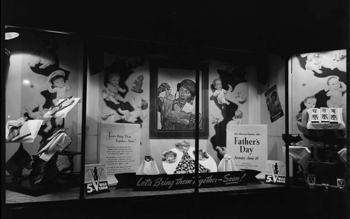 A Father's Day window display at Woodford's clothing store in downtown Laramie, 1944, shows a delighted GI holding up a baby bootie that's just arrived in a letter from home—and features a poem titled, 'Let's Bring Them Home—Soon!' American Heritage Center, University of Wyoming.