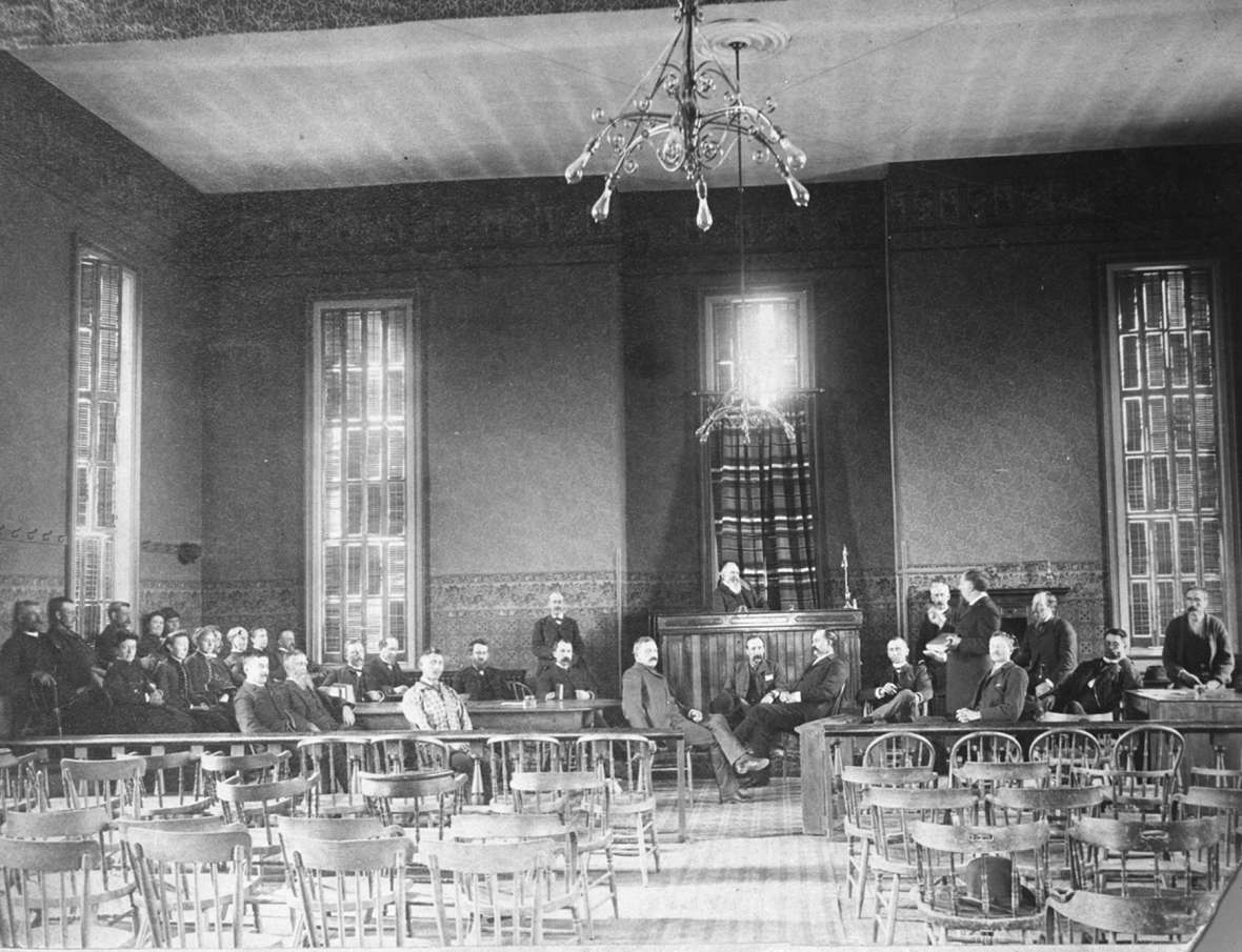 Judge Jacob B. Blair re-enacted the scene of the first woman jurors in his courtroom in Laramie in the mid 1880s. Women are seated at left in the front row of the jury box. Lawyer Melville C. Brown, the tall man at right looking at the judge, initially opposed jury service by women but later changed his mind. American Heritage Center.