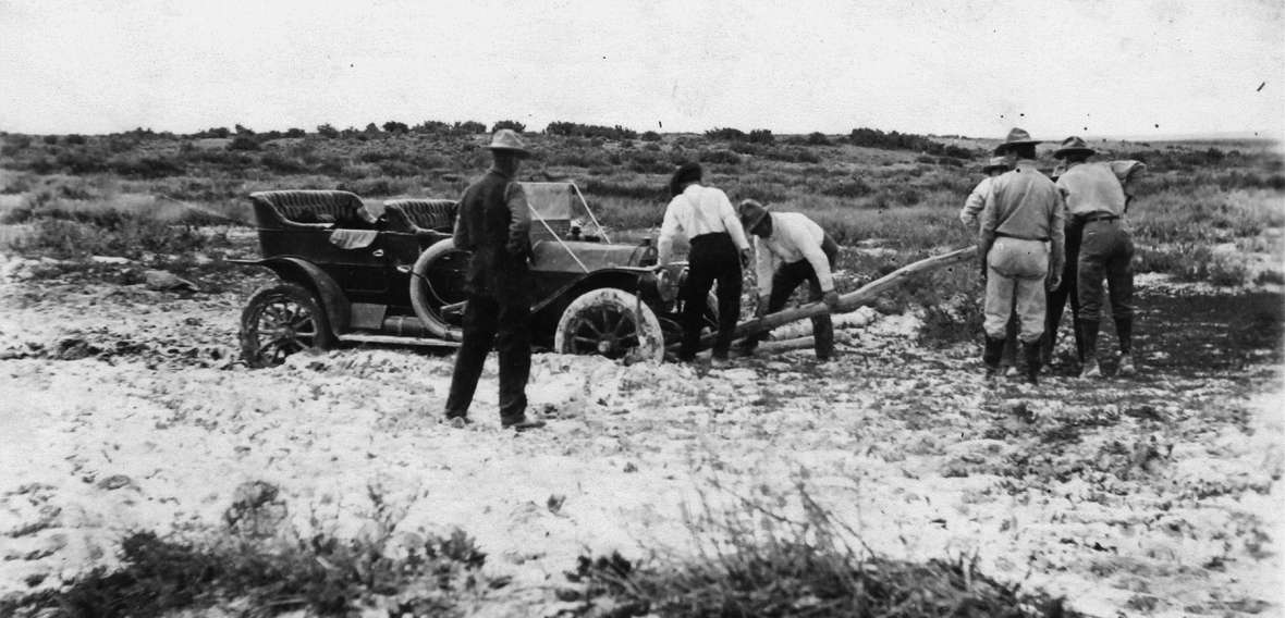 Seven men work to move a car out of the mud on the Lincoln Highway north of Laramie, Wyo., about 1915. In the early years of its existence, the highway was mostly an idea. Laramie Plains Museum.