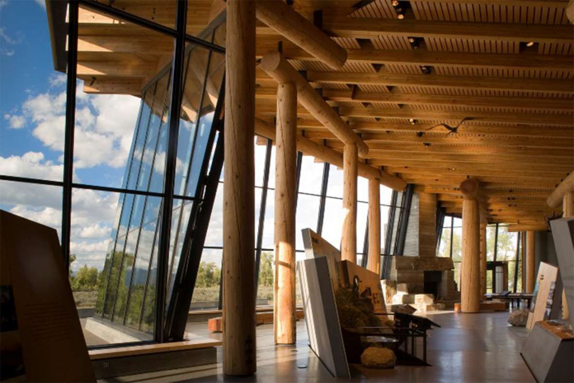 Even in buildings as recent as the 2007 visitor center in Grand Teton National Park, parkitecture's long-lived influence shows in features like the raw wood pillars and beams, and the focus on the natural setting. GNTNPF photo.