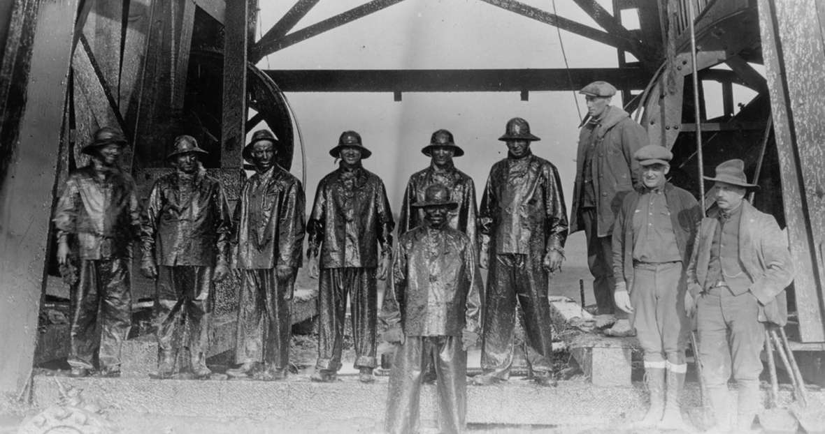 Roughnecks after capping a gusher in the Salt Creek Field, 1920s. The men on the right, who are not wearing slickers drenched in oil, are probably investors in the well. American Heritage Center, University of Wyoming.