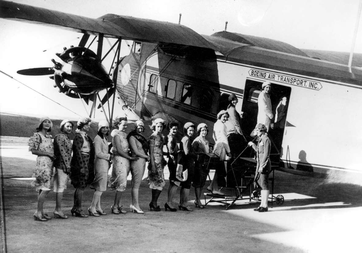 On a windy day in 1930s Cheyenne, newly recruited Boeing Air Transport stewardesses (all of them unidentified) line up to board a flight on a Boeing Model 80A aircraft. Wyoming State Archives.
