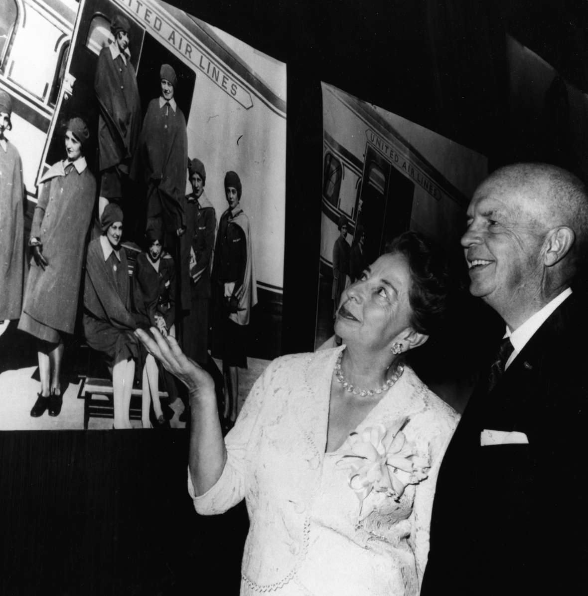 At the 30th anniversary of the United Air Lines stewardess service, Ellen Church and Steve Stimpson, the duo who first initiated the idea of hiring stewardesses, admire a photo of the original eight trained at Cheyenne in 1930. United Air Lines Archives.