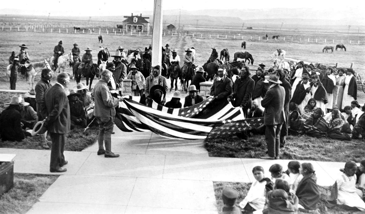 The citizenship expedtion's flag raising ceremony at Fort Washakie, Wyo., October 1913, with Shoshone and Arapaho people on hand. Joseph Dixon holds the near corner of the flag. Wyoming Veterans Memorial Museum.