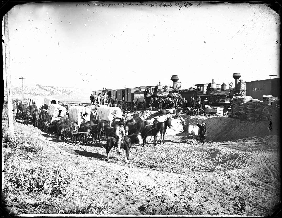 Freighters wait with teams and wagons to pick up construction supplies at the end of the Union Pacific tracks, 1868. The Trabing brothers arrived that year in Laramie, and soon began freighting goods from the railroad to far-flung parts of Wyoming Territory. A.J. Russell photo.