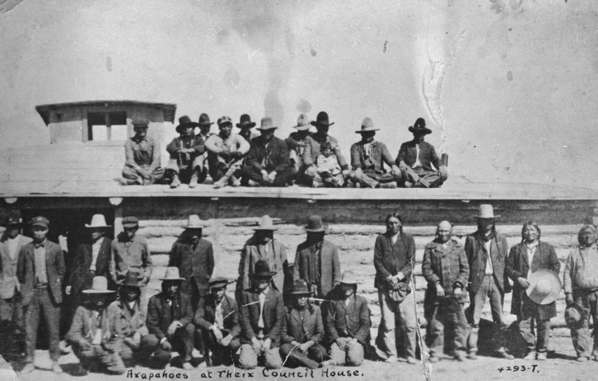 The log council house was used by both the Eastern Shoshone and Northern Arapaho tribes. Shown here—an Arapaho gathering. Riverton Museum.