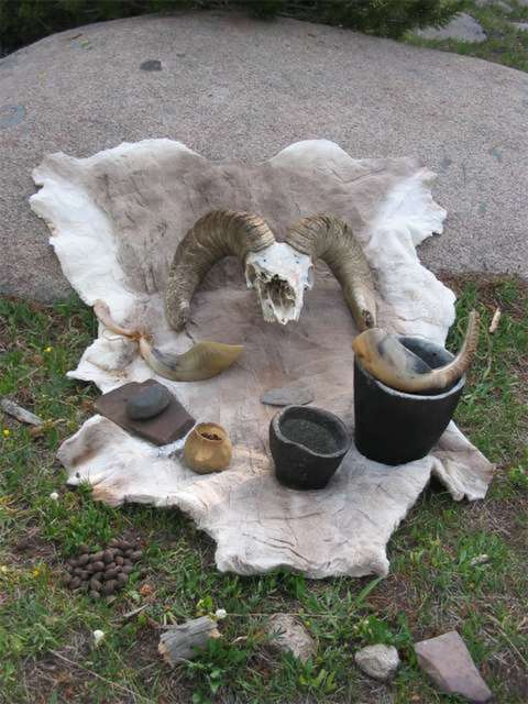 Mountain Shoshone culinary utensils and food, including sheephorn ladle, soapstone bowls, a horn-hafted stone knife, mano and metate and, in the horn bowl, rose hips--and wild mushrooms in the grass. The tools are replicas. Tory Taylor.