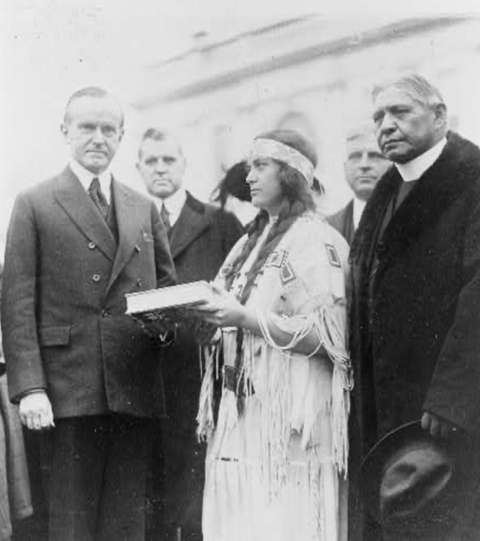 Cherokee activist Ruth Muskrat Bronson of the reformist Committee of One Hundred presents a book to President Calvin Coolidge while Sherman Coolidge looks away, 1923. Library of Congress.
