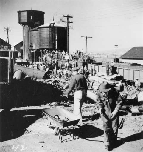 People load scrap metal into an open railroad car in Kemmerer, Wyo., 1942. Wyoming State Archives.