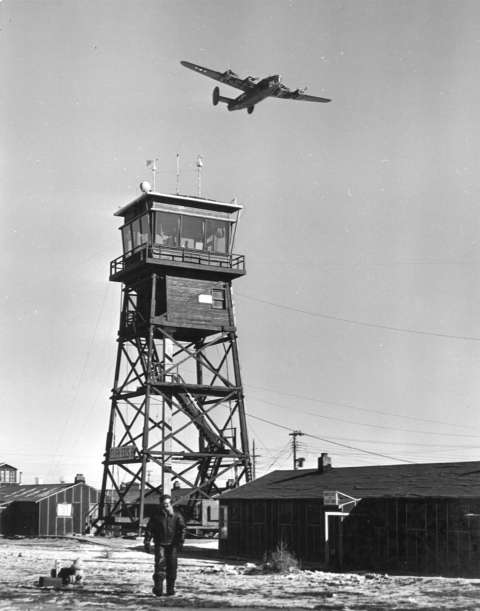 The U.S. Army Air Base in Casper opened in 1942 to train bomber crews. Here, a B-24 flies above the control tower. Casper College Western History Center.