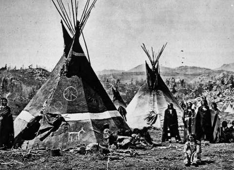 An Eastern Shoshone village near South Pass, 1870. The tipi at front bears an image of what may be the Medicine Wheel. W.H. Jackson photo.