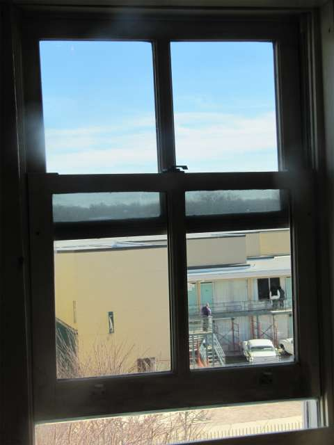 A view of the Lorraine Motel balcony where King died, through the boardinghouse window from which James Earl Ray is believed to have fired the fatal shot. Wikimedia Commons.