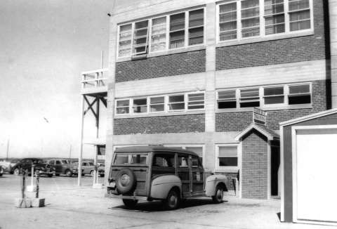 This 1951 photo shows the three-story building that housed the United Air Lines stewardess training facility at Cheyenne and a station wagon used to transport the students. Courtesy of Patricia Seibel Romeo.