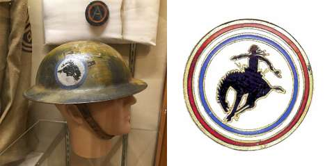 George Ostrom's helmet and a pin he made, both bearing the bucking bronco logo he designed. Wyoming Veterans Memorial Museum.