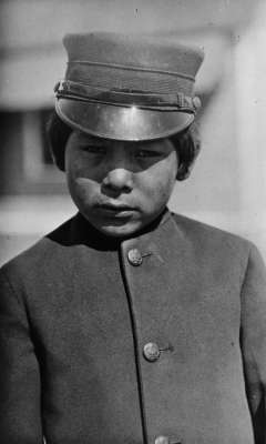 Unnamed schoolboy, at the government school near Fort Washakie, 1913. Boys at the U.S. Government boarding school, where treatment was more severe than at the mission schools, wore military uniforms. H.L. Dixon photo, Wyoming Veterans Memorial Museum collections.